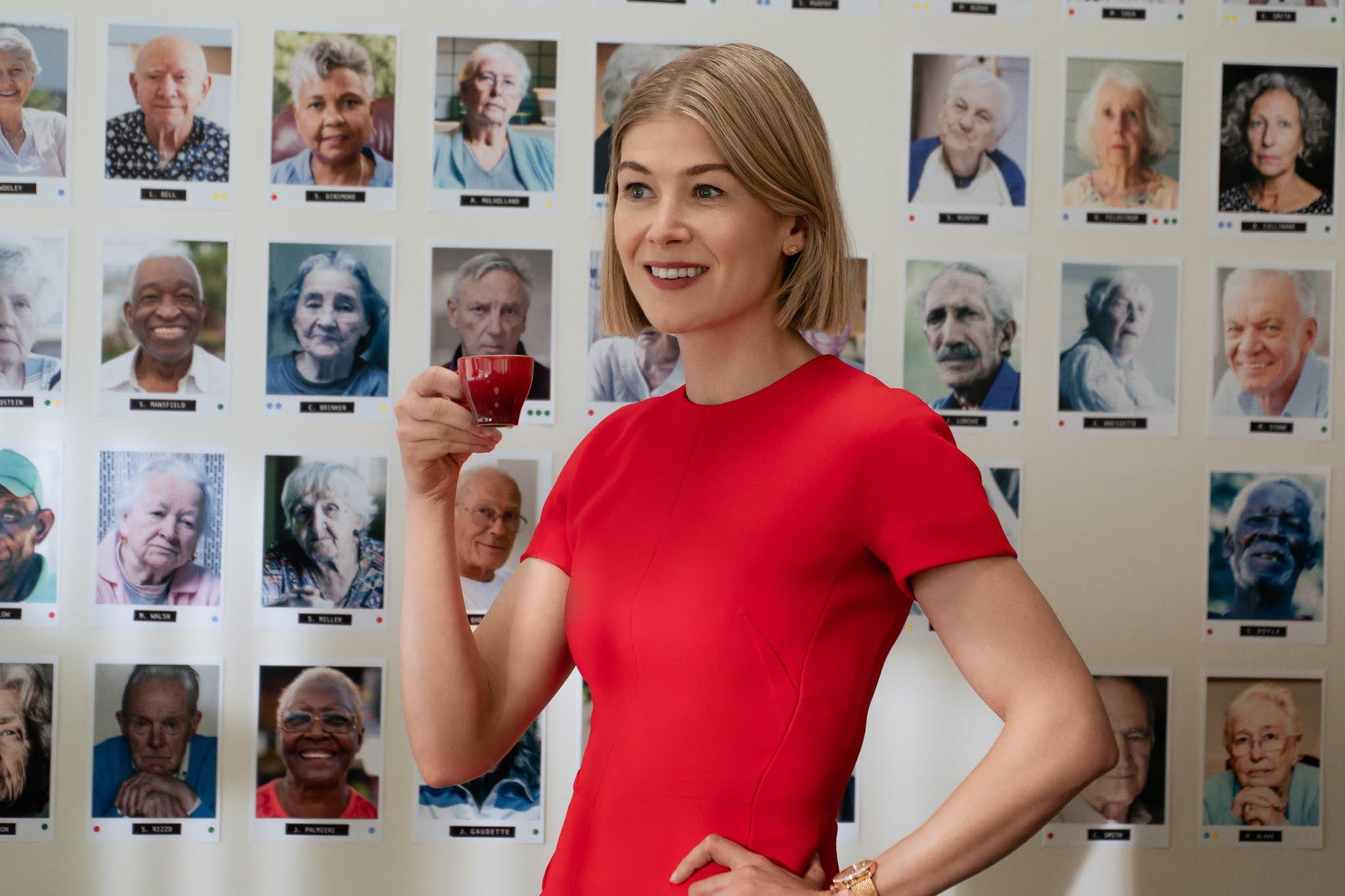 Cena do filme Eu Me Importo. No centro da imagem, a atriz Rousamand Pike, mulher branca com cabelo curto e loiro, veste uma blusa vermelha e segura uma xícara na cor vinho. O fundo da imagem é um quadro branco com diversos retratos de idosos.