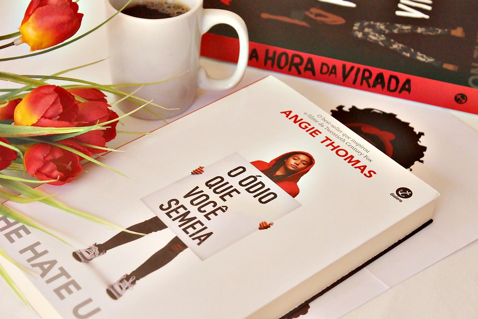Fotografia do livro O ódio que você semeia, em formato brochura e com a capa na cor branca com a atriz Amandla Stenberg na capa, segurando um cartaz com o título do livro. Amanda é uma mulher negra, com cabelos pretos e longos, ela veste um moletom vermelho, uma calça escura e tênis brancos. Ao lado do livro, há uma xícara de café e flores vermelhas ao lado; é possível ver a lombada de outro livro, com o título A Hora da Virada.