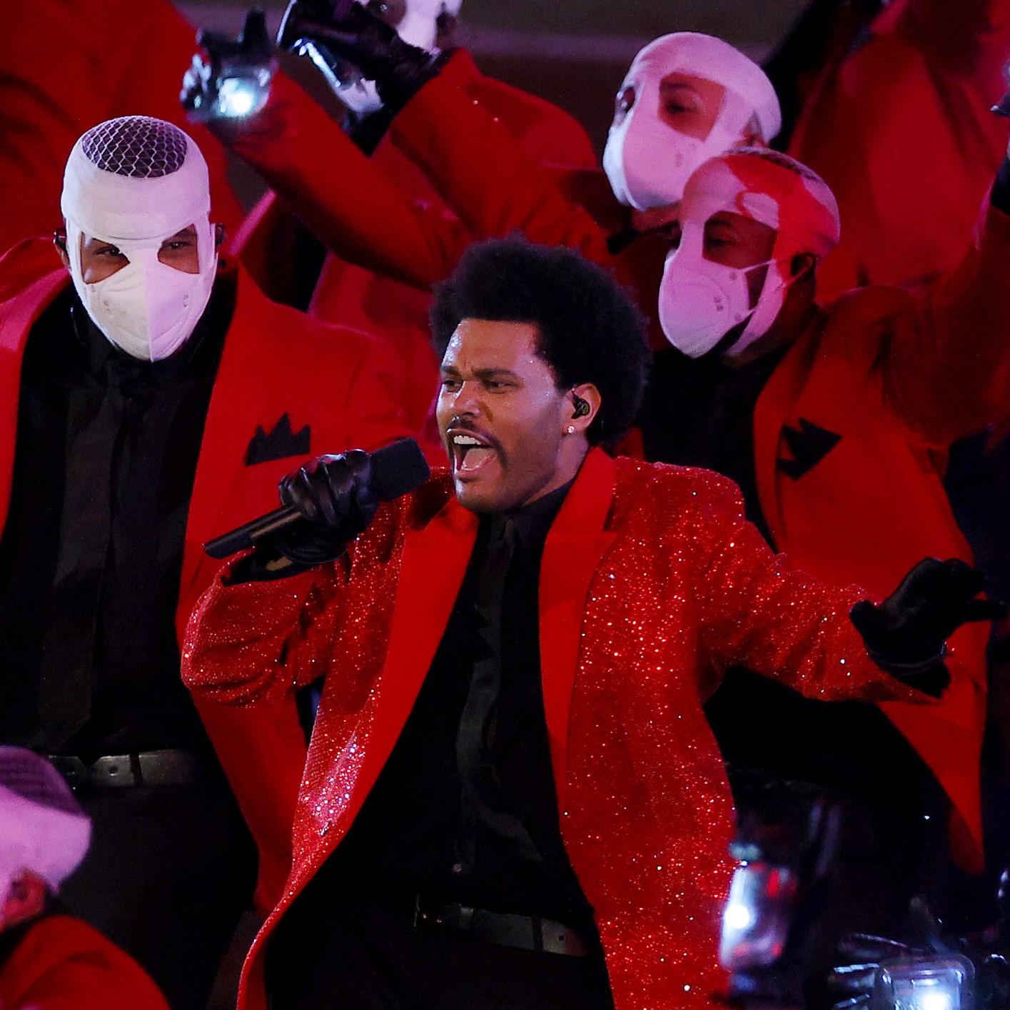 The Weeknd, um homem negro de 31 anos, está no centro da imagem. Ele usa um paletó vermelho brilhante e camisa e gravta pretas por baixo. Na sua mão direita, ele segura um microfone. A foto foi tirada no meio de um show, então sua boca está aberta e sua expressão é focada. Atrás dele, encontram-se diversos dançarinos também usando um paletó vermelho e camisa preta, mas com faixas brancas que cobrem seus rostos, deixando a mostra apenas seus olhos,