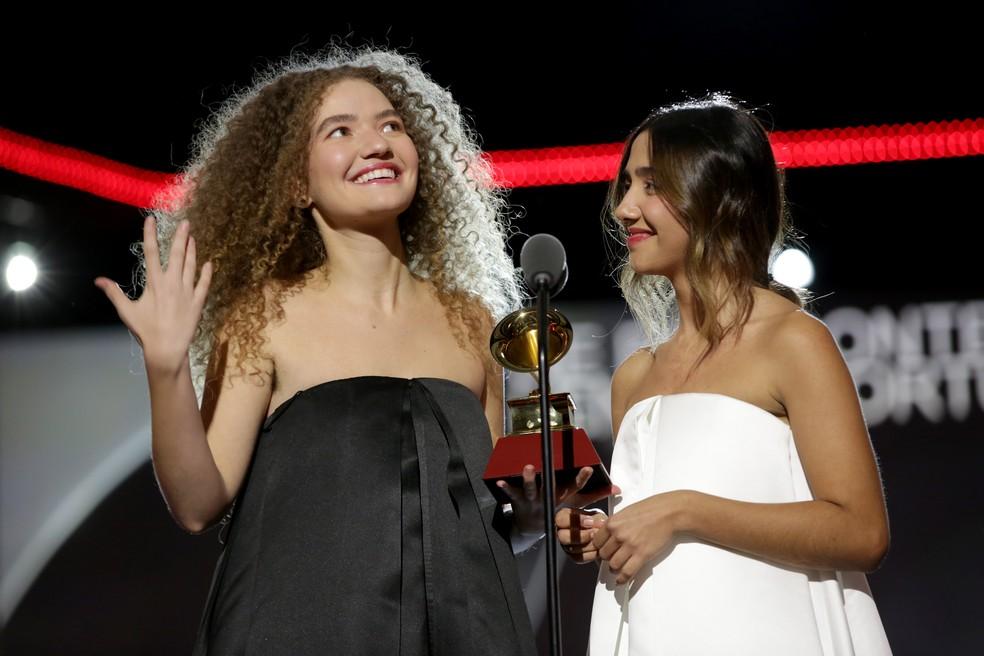 A imagem é uma fotografia da dupla ANAVITÓRIA no palco do Grammy Latino em 2019. Vitória veste um vestido preto, está com o cabelo cacheado solto. Ela segura o prêmio do Grammy, um gramofone na cor dourada . Ao seu lado, Ana usa um vestido no mesmo modelo, só que na cor branca, e o seu cabelo está preso com algumas mechas soltas. O fundo está desfocado e elas estão posicionadas atrás de um microfone.