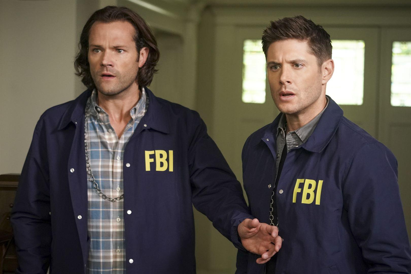 Cena de Supernatural. Sam e Dean estão vestidos com roupas do FBI, uma jaqueta azul por cima de suas roupas em um fundo claro. Eles olham espantados para algo fora da imagem e Sam está com a mão no abdômen de Dean.