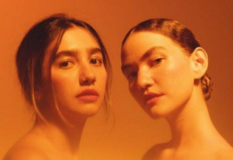 A imagem é uma fotografia de divulgação do álbum COR do duo ANAVITÓRIA. Da esquerda para a direita, Ana e Vitória usam coque no cabelo e olham fixamente para a frente. A imagem possui uma espécie de filtro amarelo e o fundo da imagem é um degradê de marrom ao amarelo.