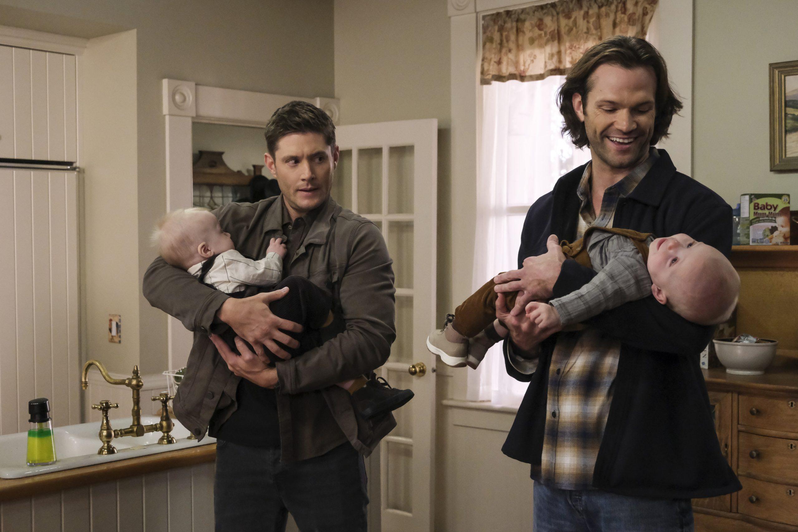 Cena de Supernatural. Sam e Dean estão segurando dois bebês. Sam está sorrindo com o bebe no colo, vestindo uma jaqueta preta por cima de uma camisa xadrez marrom. Dean está segurando o outro bebê com uma jaqueta cinza e calça escura enquanto olha para Sam. Eles estão em um banheiro, com uma pia no canto inferior esquerdo, uma porta branca atrás deles assim como uma grande janela e cômoda de madeira atrás de Sam.