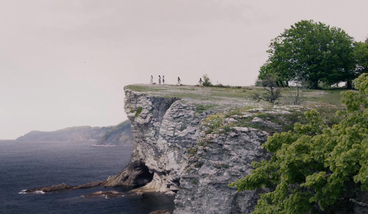 Cena do filme Silenciadas. Na imagem está de dia e 5 garotas estão ao longe, na ponta do precipício de uma montanha de pedra. Do lado esquerdo há o precipício com queda para o mar; do lado direito a montanha tem gramas e árvores grandes e verdes.