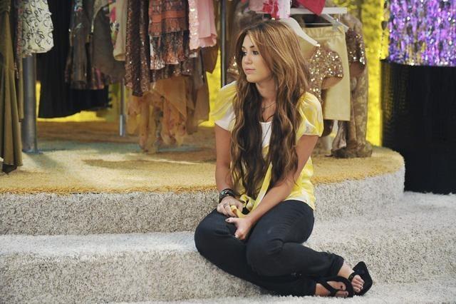 A foto tem formato retangular com uma claridade opaca. Como elemento que compõe a foto, temos um palco de dois andares coberto por um carpete de pelos. Ao fundo, no topo do palco, em desfoque, temos um varal de roupas coloridas e brilhantes. No centro da imagem, sentada no primeiro degrau do palco, temos a personagem Miley Stewart que olha tristemente para o canto inferior esquerdo da foto. Seu cabelos tem um tom de castanho escuro nas raízes e um tom de castanho claro que se estendem até o caimento dos fios na altura de sua barriga. Miley veste uma blusa amarela de manga curta, uma calça justa preta e um chinelo preto de correia dupla.
