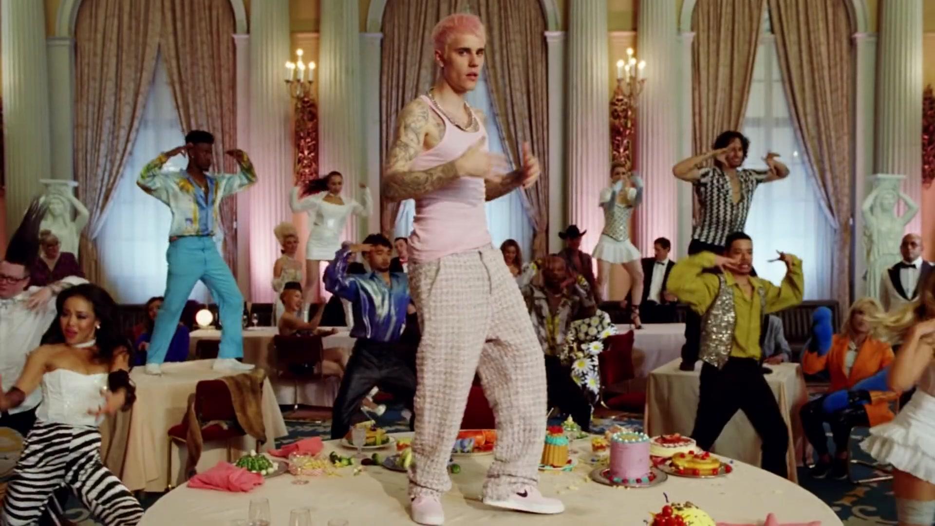 A imagem é uma cena do videoclipe da música Yummy, de Justin Bieber. Na imagem, há um salão de jantar com várias mesas espalhadas. Ao centro, o cantor Justin Bieber está em cima de uma mesa, dançando. Justin é um homem branco, de cabelos lisos curtos e pintados de rosa claro, ele veste uma regata, calça xadrez larga e um par de tênis em tons de rosa. Ao fundo, há outras pessoas dançando em cima das mesas e espalhadas pelo salão, todos vestem roupas bem coloridas.
