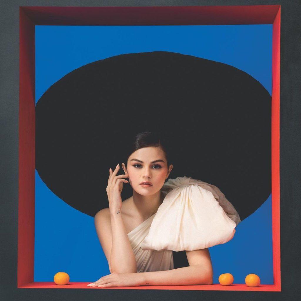 Selena Gomez está com o cabelo preso, usando um chapéu preto gigante, com um vestido bege de um ombro só. O vestido tem um laço gigante no ombro. Ela está com a mão no queixo e ao seu lado têm três laranjas, duas à direita e uma à esquerda. Em seu braço existe uma tatuagem de nota musical. O fundo da imagem é azul, com uma borda vermelha, parecendo uma janela ou um quadro.