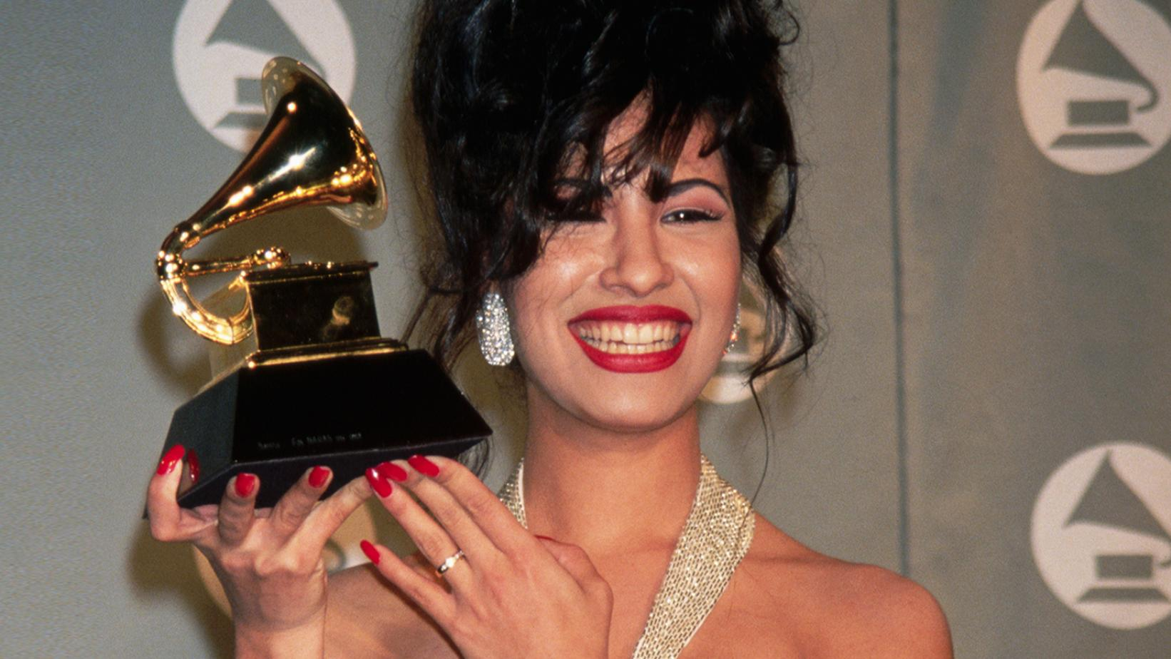 Selena Quintanilla, uma mulher branca de cabelo preto, está segurando seu gramofone dourado. Ela está de cabelo preso, com a franja no rosto, brincos brilhantes e unhas grandes pintadas de vermelho. Ela está sorrindo, com um batom vermelho e a alça de seu vestido é brilhante. Na mão em que está segurando o Grammy, ela usa um anel prata.