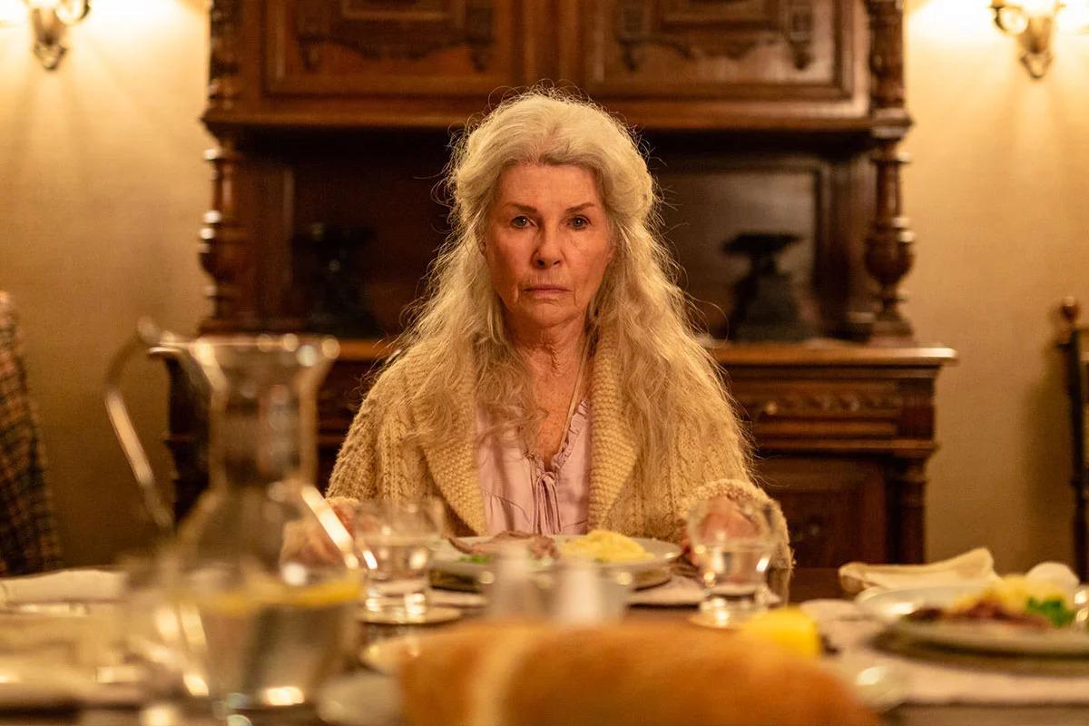 Cena do filme Relic. Robyn Nevin, uma mulher de 78 anos, está sentada na ponta de uma mesa. Ela está no centro da imagem e olha para frente, com os olhos vidrados. Seu cabelo é grisalho e comprido e ela usa uma blusa rosa embaixo de um casaco branco de crochê. A sua frente, a mesa está embaçada, assim como os patros e alimentos em cima dela. Atrás, encontra-se um móvel de madeira parecido com uma estante.