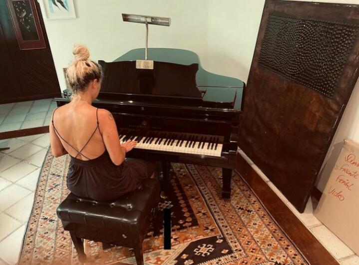 Foto da cantora Tiê ao piano. No centro da foto, vemos a cantora Tiê de costas, sentada numa banqueta acolchoada preta, e com as mãos sobre o piano. Ela é uma mulher branca, de 40 anos, com cabelos que estão com a raiz castanho escuras e o resto descolorido em um tom alaranjado sutil. O cabelo comprido está preso em um coque e ela usa um vestido preto longo que deixa as costas à mostra. O piano a sua frente é preto, com uma meia cauda e há uma luminária e desligada em cima da estante de partituras.