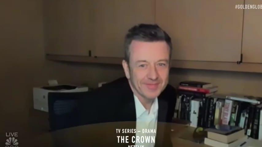 Foto de Peter Morgan recebendo o prêmio por The Crown, série que é produtor. Ele é um homem branco de 57 anos, e veste um paletó preto com uma camisa branca por baixo. Ao fundo da imagem podemos ver armários de escritórios, livros e uma impressora.