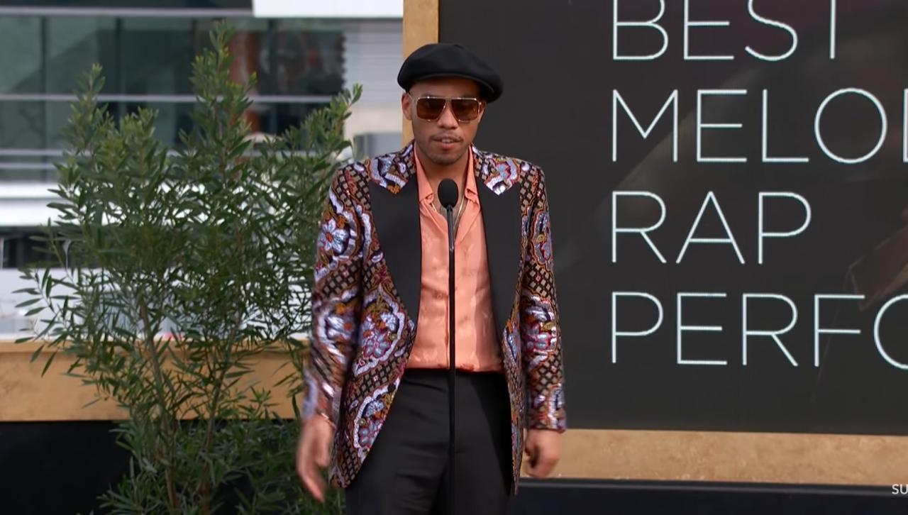 Foto de Anderson Paak. O homem negro, usando boina e calça preta, blusa laranja, jaqueta colorida e oculos escuro. Ele está em pé na frente do microfone dando seu discurso. No fundo há uma planta do lado esquerdo e o telão do grammy do lado direito, onde está escrito o nome da categoria.