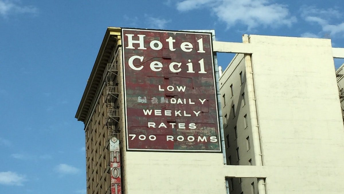 Foto do Hotel Cecil. O hotel é bege, com uma grande placa vermelha no que anuncia HOTEL CECIL - LOW DAILY WEEKLY RATES - 700 ROOMS. A fachada está desgastada e o céu no fundo é azul.
