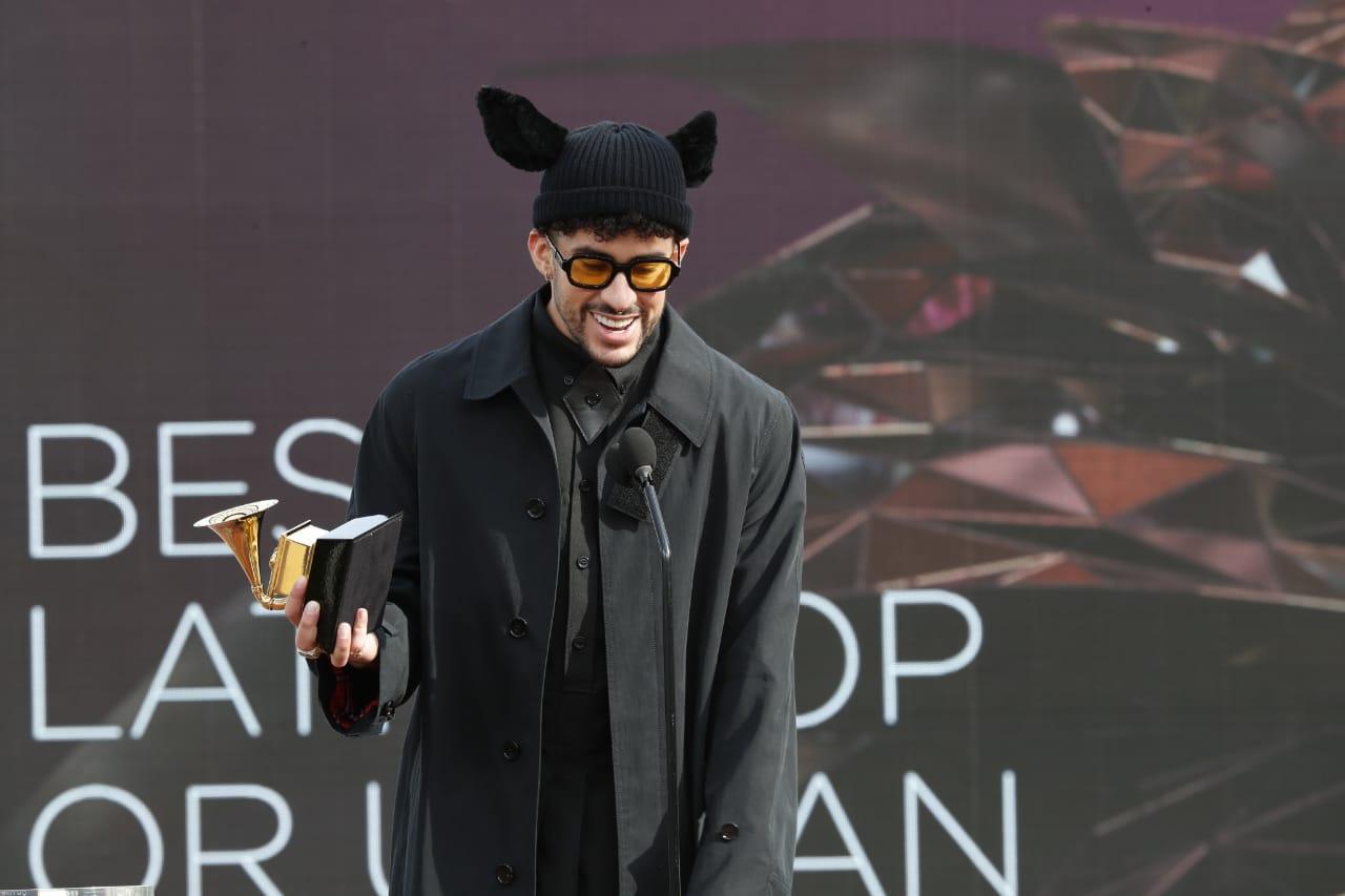 """Foto do cantor Bad Bunny. Um homem latino de cabelos pretos e cacheados e barba. Ele veste uma roupa preta e um sobretudo preto. Ele usa uma touca preta com duas orelhas de coelha também pretas. Um óculos de armação preta e lentes amarelas. Na sua mão esquerda há um Grammy. Na sua frente há um microfone. O fundo é roxo e no canto inferior esquerdo lê-se em branco """"BEST LATIN POP OR URBAN"""""""
