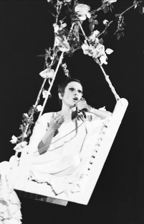 Fotografia de Elis Regina apresentando seu espetáculo Falso Brilhante. Na imagem, a artista está sentada em um balanço de madeira suspenso no palco, decorado por flores. Ela segura um microfone com a mão esquerda e olha para o público, cantando. Elis usa um vestido branco de mangas e o fundo da imagem é preto. A imagem é em preto e branco.