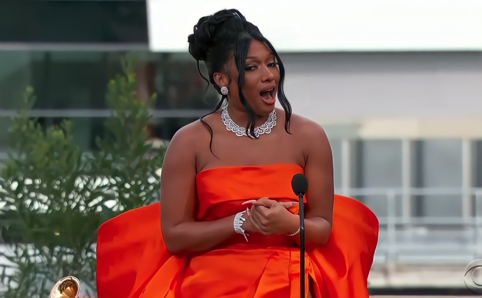 Foto da cantora Megan Thee Stallion. Ela está na parte central da imagem. Usa um vestido laranja. Colar, brinco e pulseira pratas. Ela está com as mãos juntas e na sua frente há um microfone. Ao lado direito vemos parte de uma casa. Ao lado esquerdo vemos folhas verdes de uma árvore e um Grammy.