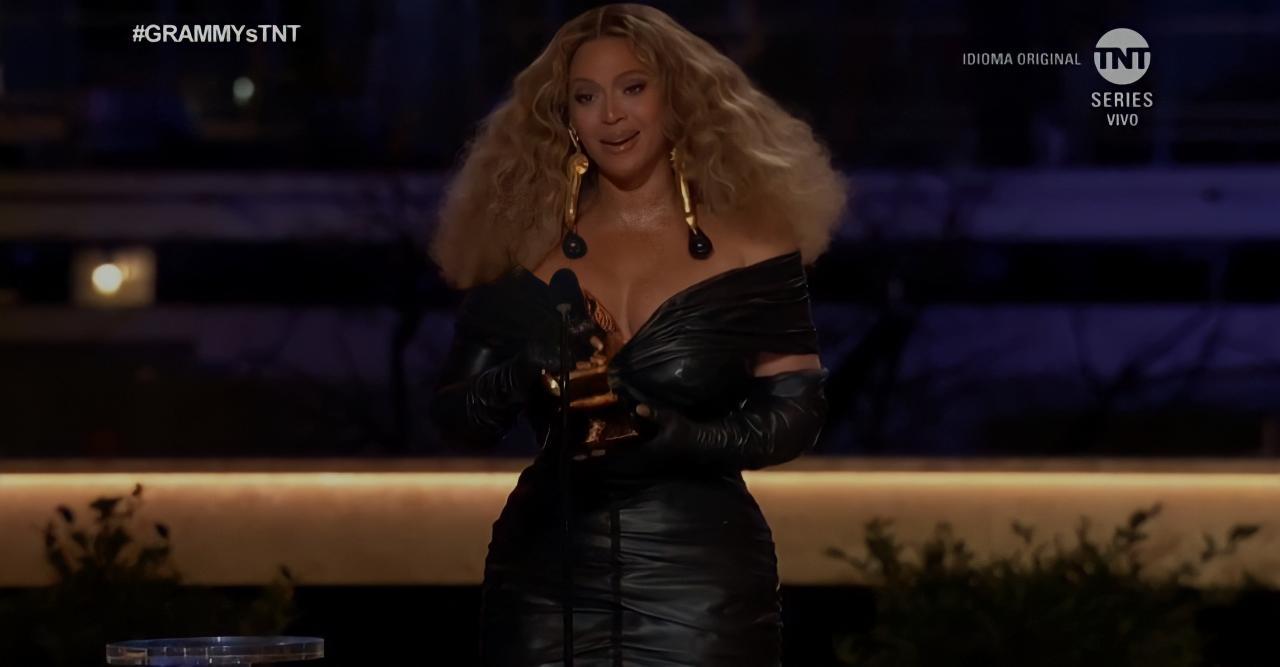 Foto da cantora Beyoncé. A mulher magra e negra de cabelo cacheado loiro, veste um vestido preto e usa um par de brincos dourados. Ela segura seu grammy, enquanto fala no microfone a sua frente. Atrás dela, é possível ver um fundo roxo e plantas no chão.