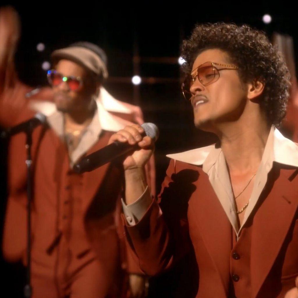 Imagem da apresentação de Bruno Mars e Anderson .Paak no Grammy 2021. Na imagem, Bruno, um homem negro de cabelos cacheados, veste um terno e óculos de sol levemente transparentes, ambos da cor caramelho, e está do lado esquerdo, mais à frente. Anderson, também um homem negro, veste a mesma roupa de Mars e um óculos também caramelo mas com brilho prateado ao redor das lentes e uma boina marrom, e está do lado direito, um pouco mais ao fundo. Os dois estão cantando e ao fundo da imagem pode-se observar a cenografia do palco, tomada apenas por um fundo escuro que imita um céu estrelado.