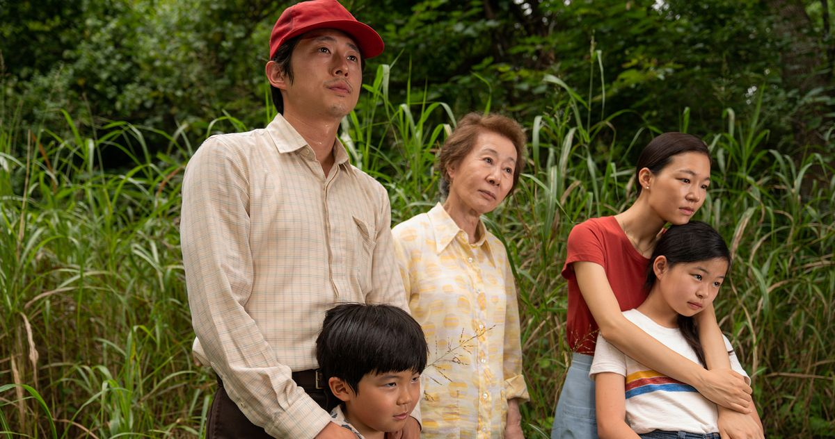 Cena do filme Minari. Uma família de sul-coreanos está na foto. Da esquerda para a direita: Jacob usa um boné vermelho, camisa de mangas compridas branca e calça marrom; David, um menino de 8 anos, está do busto para cima. Seu cabelo é preto e cobre sua testa; Soonja, uma senhora, usa uma camisa branca com figuras amarelas. Seu cabelo é castanho e curto; Monica, uma mulher adulta, usa blusa vermelha, e seu cabelo é preto e comprido; Anne, uma jovem, usa blusa branca com listras amarelas, azuis e vermelhas. Seu cabelo é preto e comprido. Ao fundo, vemos folhagens verdes.