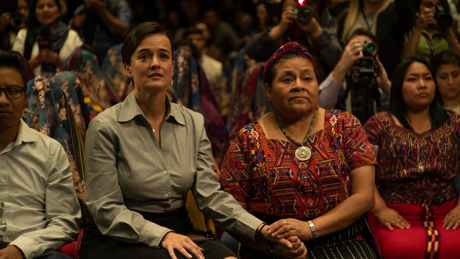 Cena do filme La Llorona. No centro e à direita da imagem vemos Rigoberta Menchú, uma mulher indígena, com um colar verde e branco, uma faixa roxa no cabelo e uma camisa laranja com detalhes indígenas em azul, branco e preto. Ela segura as mãos de uma mulher branca à sua esquerda, com uma camisa social cinza e cabelos presos. As duas estão sentadas e possuem uma feição curiosa e esperançosa. Atrás, várias outras mulheres de origem maia-ixile e jornalistas estão sentadas.