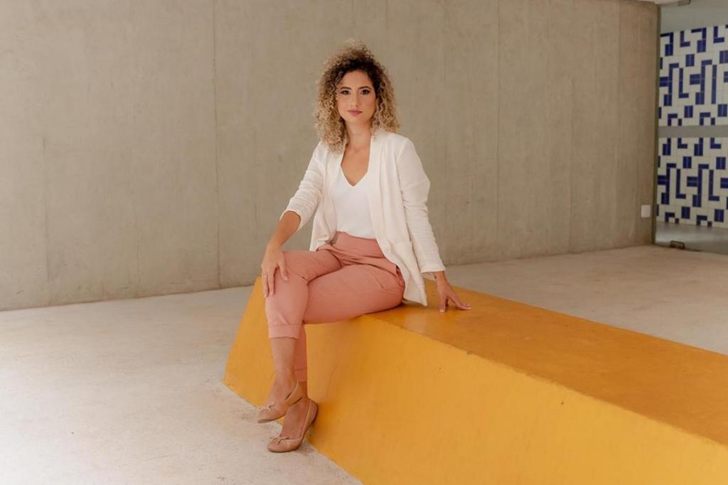 A foto é retangular e centraliza a autora Fabiane Guimarães. Fabiane é uma mulher de 30 anos com cabelo crespo e castanhos, com as pontas mais claras. Ela usa uma blusa e um blazer brancos e uma calça rosé. Ela está com as pernas cruzadas e uma mão apoiada no joelho. Ela está sentada em um banco de concreto amarelo, olhando diretamente para a câmera. Ao fundo, o cenário é bege, paredes e piso. No canto direito, há o início de uma parede branca com padrões azuis.
