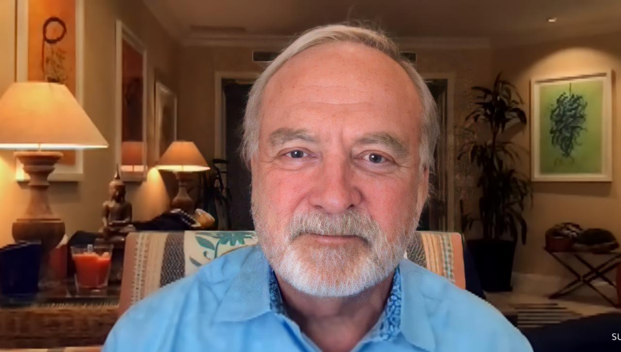 Foto de James Keach. Homem branco de olho azul com barba e cabelo branco. Ele veste uma camiseta azul. Está sentado em um banco colorido em uma sala, e atrás é possível ver uma planta, alguns quadros, abajures e mais alguns objetos de decoração.