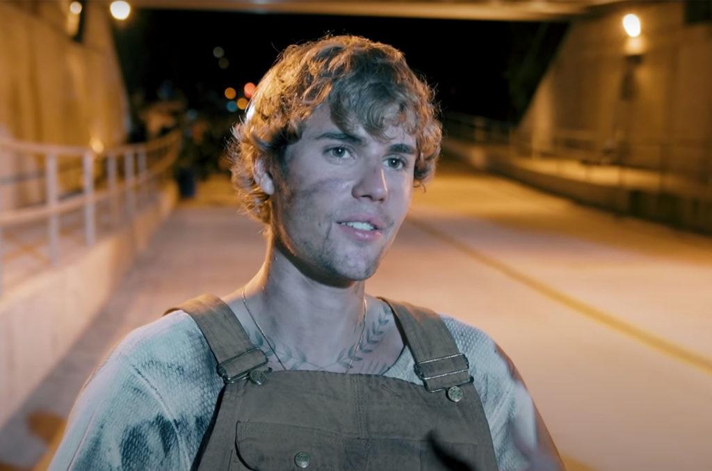 A imagem é uma cena do videoclipe da música Holy, de Justin Bieber. Na Imagem, Justin está dentro de um viaduto. O cantor está com os cabelos lisos e loiros, com a cara suja de graxa, ele veste uma blusa suja e um macacão marrom claro.