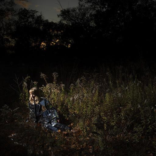 Capa do disco Ignorance, da banda The Weather Station. Na foto, está de noite, mas vemos Tamara Linderman, uma mulher branca, loira e de roupas jeans, sentada no matagal. A luz foca nela e mostra um pouco do mato verde ao seu redor, ao fundo vemos sombras de floresta, árvores e arbustos.