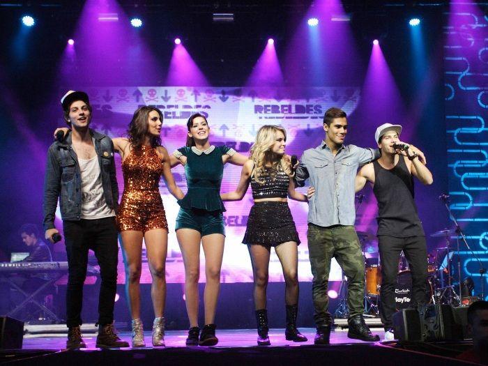 Foto dos seis integrantes do grupo Rebeldes em um de seus shows na seguinte sequência: Tomás/Chay, Carla/Mel, Alice/Sophia, Roberta/Lua, Pedro/Micael e Diego/Arthur.