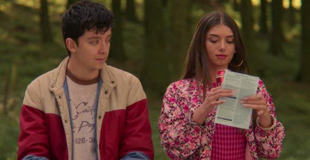 Cena da série Sex Education. Asa Butterfield, que interpreta Otis, é um jovem branco de cabelos escuros e veste uma jaqueta vermelha e azul. Ele olha para Mimi Keene, que interpreta Ruby, ao seu lado. Ela é uma jovem branca, com cabelos lisos e castanhos, usa uma jaqueta rosa e segura um refrigerante. Ambos estão em um campo.