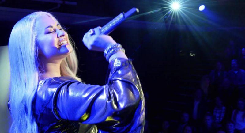 Cena do filme Festival Eurovision da Canção: A Saga de Sigrit e Lars. Na esquerda da imagem, a atriz Demi Lovato, mulher branca com cabelos compridos loiros, está cantando e segurando um microfone com os olhos fechados. Ela veste um vestido roxo com mangas compridas. No fundo da imagem é possível perceber uma plateia. A foto possui um foco de luz na cor azul.