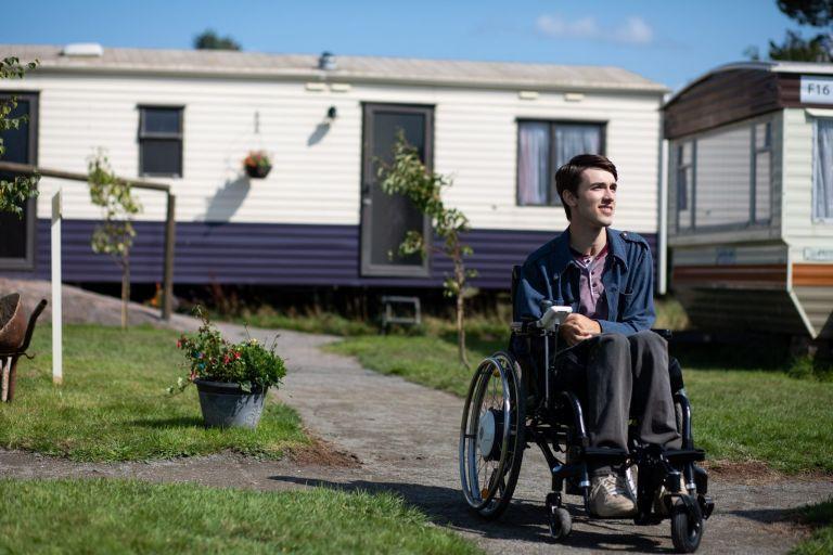 Cena da série Sex Education. Na imagem, George Robinson, que interpreta Isaac; ele é um homem branco de cabelos castanhos. George veste uma blusa lilás, com jaqueta azul por cima, e uma calça jeans escura. Ele é portador de deficiência física e está em uma cadeira de rodas. Ao seu redor existem trailers e plantas.