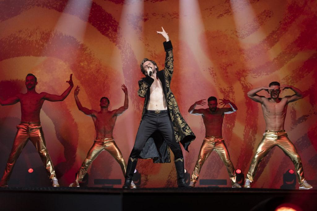 Cena do filme Festival Eurovision da Canção: A Saga de Sigrit e Lars. O ator Dan Stevens está localizado no centro da imagem, em cima de um palco. O ator é um homem branco, jovem e com cabelos e barba loiro claro. Ele veste uma calça preta e um casaco preto com detalhes dourados. Ele canta e está com a mão esquerda levantada. Em cada lado do ator, há 2 homens sem camisa vestindo somente calças douradas.