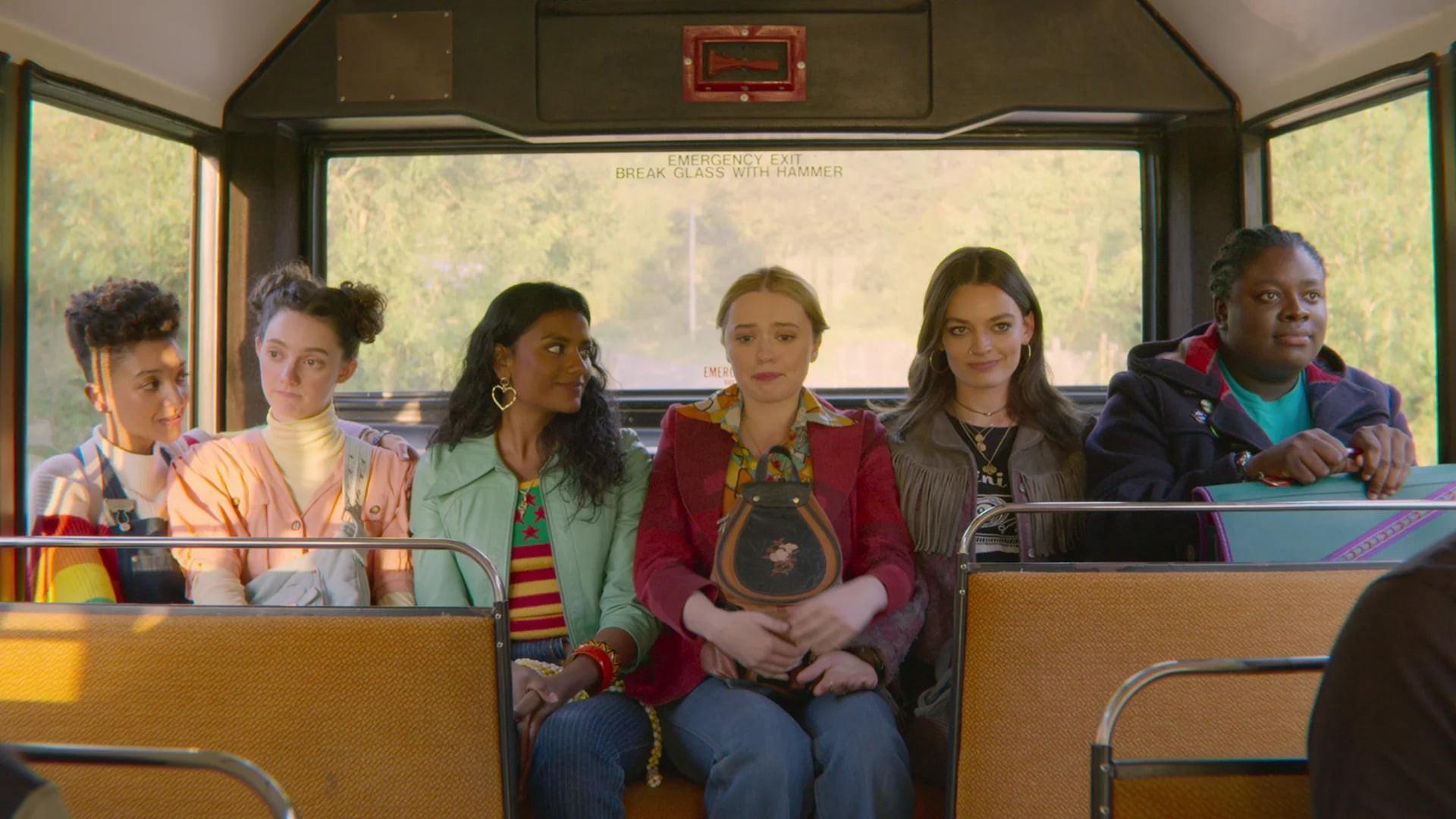 Cena da série Sex Education. Na imagem, há seis personagens mulheres. Da esquerda para a direita, está Ola, que é uma mulher negra de cabelos cacheados curtos. Ela usa um macacão jeans e olha para o lado direito; ao seu lado, está Lily, que é uma mulher branca, tem cabelos castanhos em dois coques. Ela usa uma blusa rosa claro e olha para o lado esquerdo; em seguida, está Olivia, que é uma mulher marrom de cabelo preto cacheado. Ela usa uma blusa verde e olha para a direita; Aimee, uma mulher branca de cabelos louros, sorri ao seu lado. Ela usa uma jaqueta vermelha e está abraçada a sua mochila; Maeve, mulher branca de cabelos castanhos, segura a mão de Aimee. Ela sorri e olha para frente. Veste uma jaqueta escura com franjas; Viv é uma mulher negra, tem tranças em seu cabelo. Ela segura sua mochila e sorri olhando para frente. Elas estão sentadas no fundo de um ônibus.