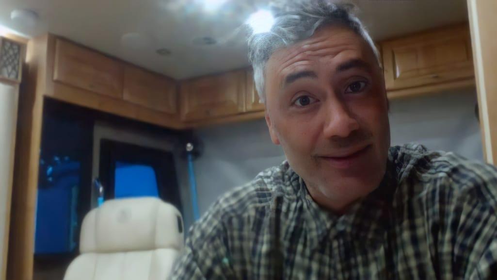 Foto de Taika Waititi. O homem branco magro e de cabelo cinza, olha para a câmera com uma expressão de surpresa. Ele veste uma camiseta quadriculada verde e azul. No fundo é possível ver armários marrons em uma parede branca, e uma janela.