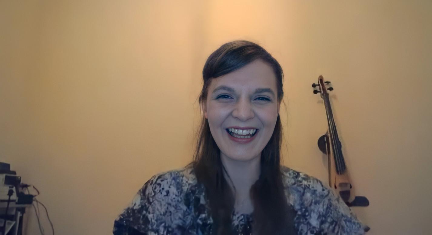 Foto de Hildur Gudnadottir. A mulher branca e magra de cabelo escuro olha para a câmera sorrindo. Ela veste uma blusa branca com manchas em azul. Atrás há uma parede branca lisa, onde está pendurado um violino bege.