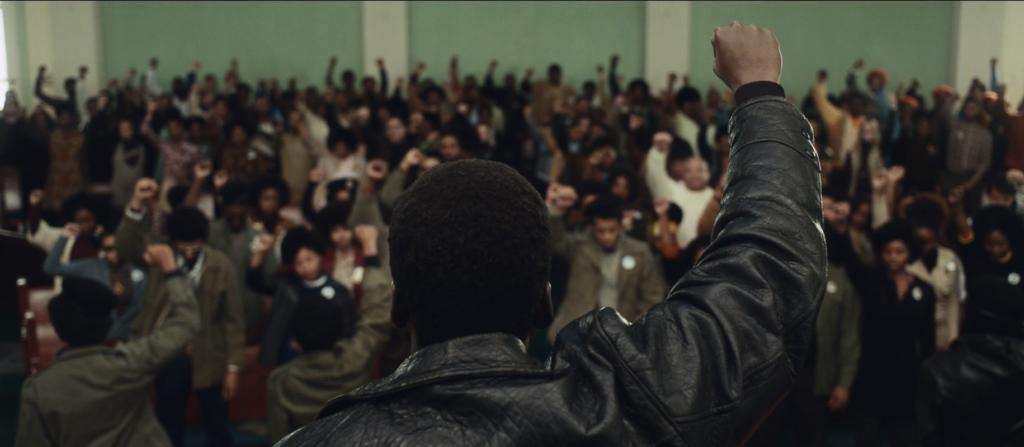 Cena do Filme Judas e o Messias Negro. A imagem mostra o personagem Fred Hampton, interpretado por Daniel Kaluuya, um homem negro, ao centro e de costas. Ele tem os cabelos crespos curtos, veste uma jaqueta de couro, e está levantando a mão direita com o punho fechado em um púlpito. À sua frente, existe uma multidão de pessoas o assistindo e de pé repetindo o gesto.