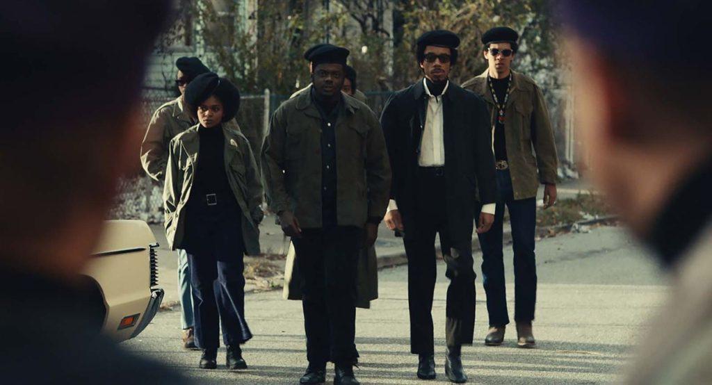 Cena do filme Judas e o Messias Negro. Na imagem, vemos o personagem Fred Hampton, interpretado por Daniel Kaluuya, seguido pelos demais companheiros dos Panteras Negras. Todos eles estão vestidos de preto, com casacos verde musgo, botas, óculos de sol e boinas pretas. Eles estão caminhando em direção à câmera por uma rua, ao fundo estão árvores e uma cerca gradeada, nas laterais da imagem nota-se o contorno desfocado de dois rostos de homens brancos.