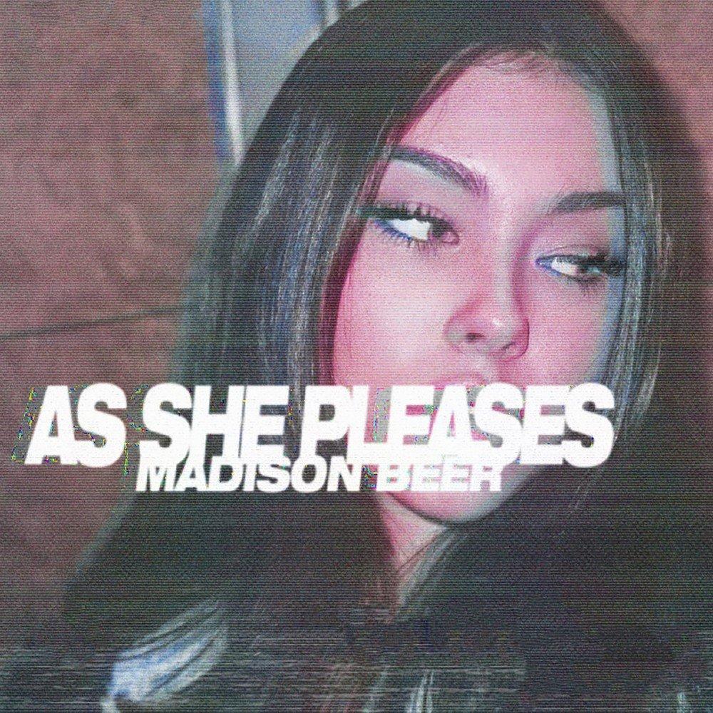 """Capa do ep As She Pleases. Uma foto com efeito rosa do rosto de Madison, mulher branca de cabelos pretos, olhando para o lado direito. No meio, está escrito """"AS SHE PLEASES / MADISON BEER"""" em branco."""