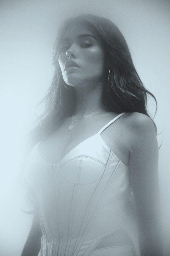 Uma foto de Madison Beer tirada de baixo. A mulher branca de cabelos castanhos olha para a câmera, vestindo uma blusa branca. A foto foi editada em preto e branco.