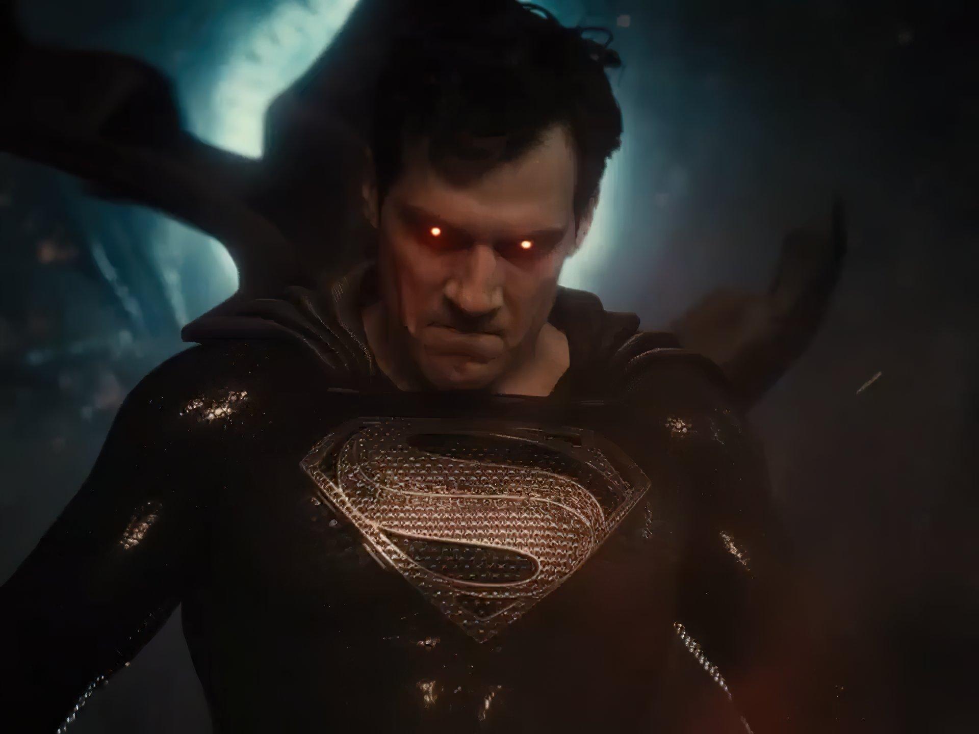 """Superman (Henry Cavill) encara furiosamente a câmera, com seus olhos brilhando avermelhados, momentos antes de sua visão de calor atingir o alvo. Ele usa uma versão inteiramente preta de seu uniforme clássico, salvo pelo """"S"""" prateado, brilhando no peito e adornado por pequenos entalhes."""