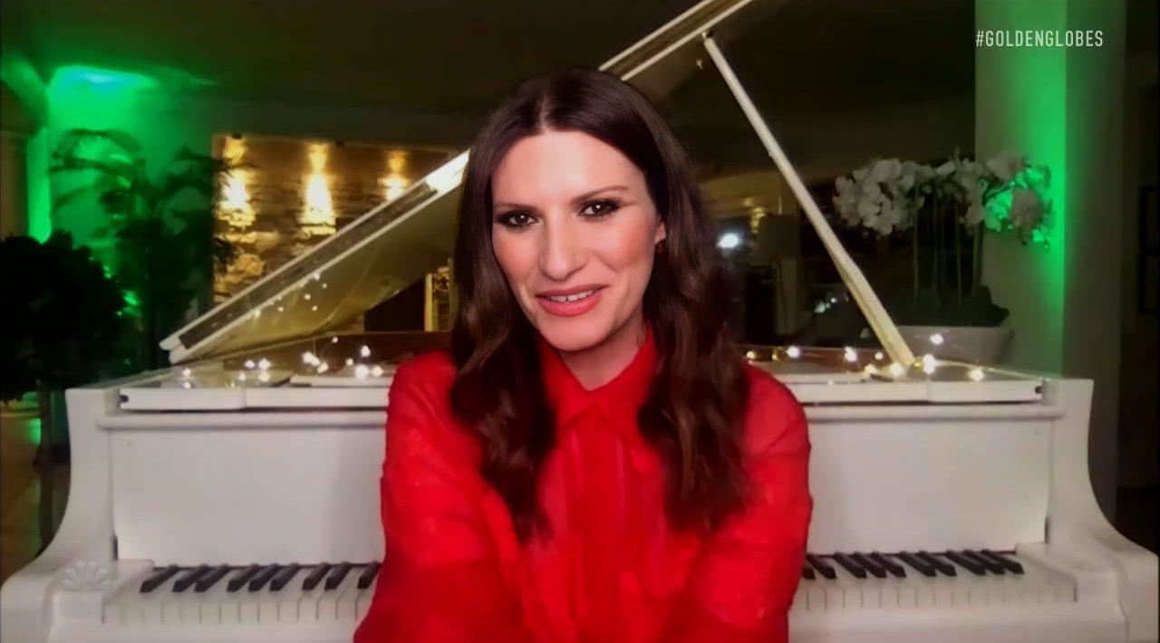 Foto da cantora Laura Pausini. Uma mulher branca, de cabelos castanhos. Ela veste uma blusa vermelha. Ao fundo vemos um piano branco. À direita um vaso branco com flores brancas. À esquerda uma parede branca e árvores com luzes verdes.