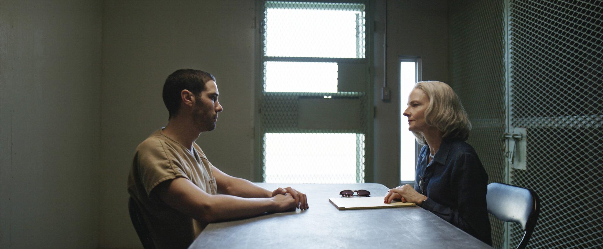 Cena do filme The Mauritanian. Vemos Tahar Rahim e Jodie Foster sentados frente a frente, separados por uma mesa de ferro, o cenário é uma sala de presídio. Tahar veste uma camiseta bege e tem as mãos na mesa. Ele tem pele marrom clara e cabelos pretos rente à cabeça. Jodie veste blusa azul escuro e tem o cabelo grisalho e na altura dos ombros. Eles se olham nos olhos. Jodie tem uma pasta e um celular prostrados na mesa à sua frente.