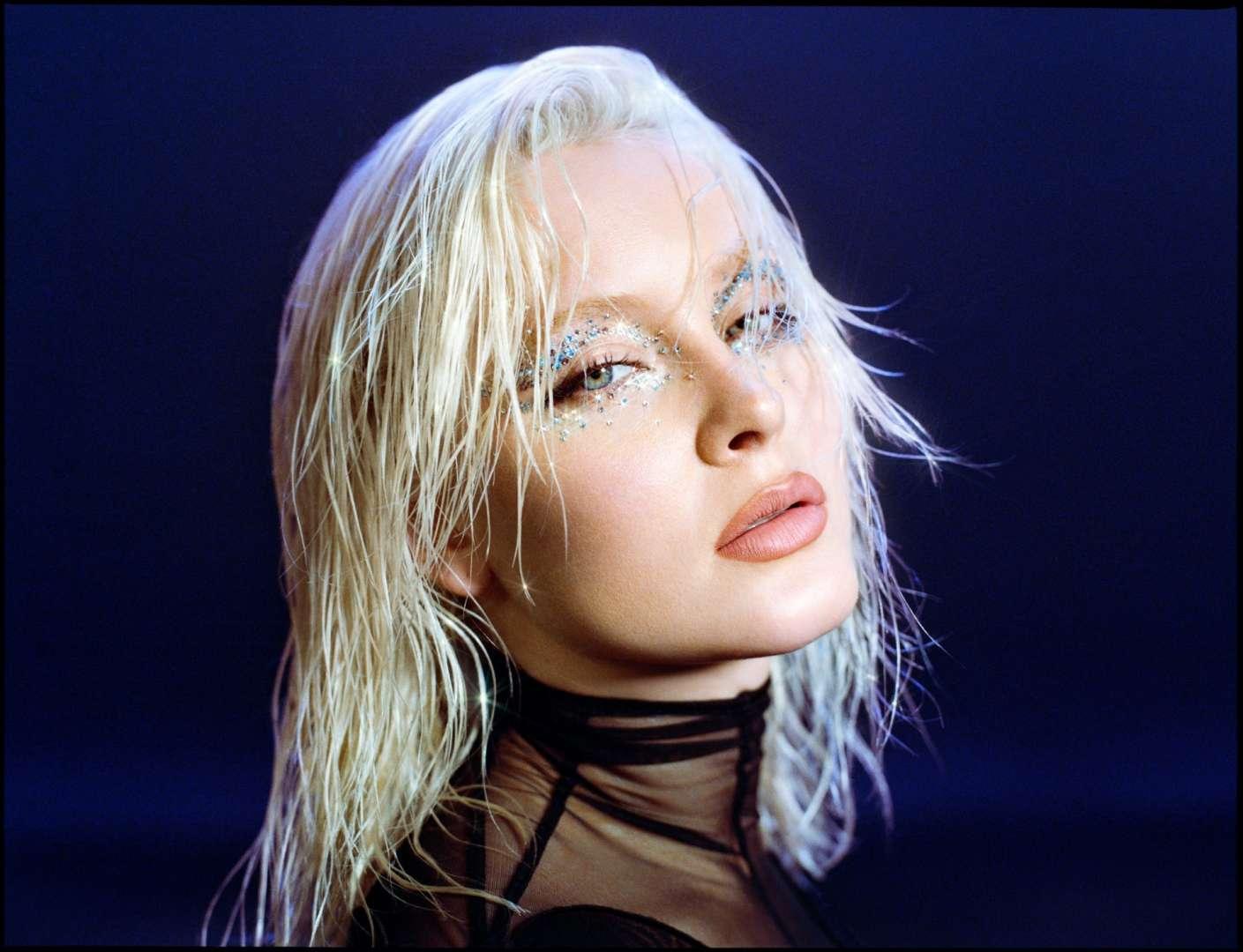 Foto de Zara Larsson. Sobre um fundo azul, a cabeça de Zara aparece. Seus cabelos platinados estão molhados e sua franja cobre levemente seus olhos. Com uma maquiagem brilhante que contorna seus olhos, ela tem aparência séria. Zara usa uma blusa com bordas pretas e cobertura transparente.