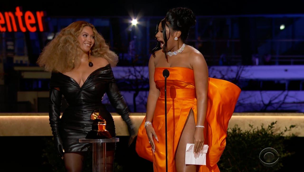 Foto das cantoras Megan Thee Stallion e Beyoncé. À esquerda temos Beyoncé, uma mulher negra com cabelos loiros na altura dos ombros. Ela usa um vestido decotado preto e luvas que vão acima do cotovelo, alcançando as mangas do vestido. Ela está sorrindo e olhando para Megan. À direita, Megan usa um vestido laranja sem alças, seu cabelo preto está preso em um coque e ela usa brincos, pulseiras e colar pratas. Em sua mão esquerda há uma folha de papel. Ela está de boca aberta e a sua frente há um microfone. Na frente das duas tem um Grammy. O fundo é azul desfocado, com algumas plantas verdes no canto inferior direito.