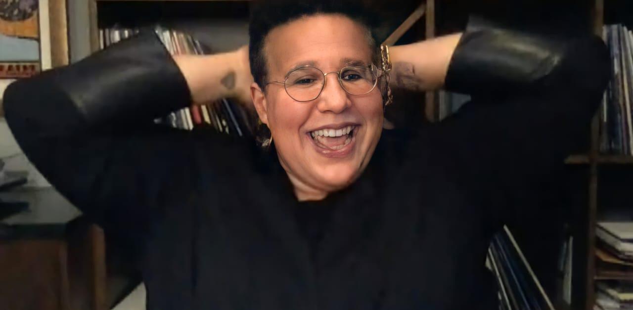 Foto de Brittany Howard. Mulher negra de pele clara, gorda e de cabelo curto. A cantora sorri, com as mãos atrás da sua cabeça. Ela veste terno preto e usa óculos da mesma cor. No fundo é possível ver uma estante marrom cheia de livros.