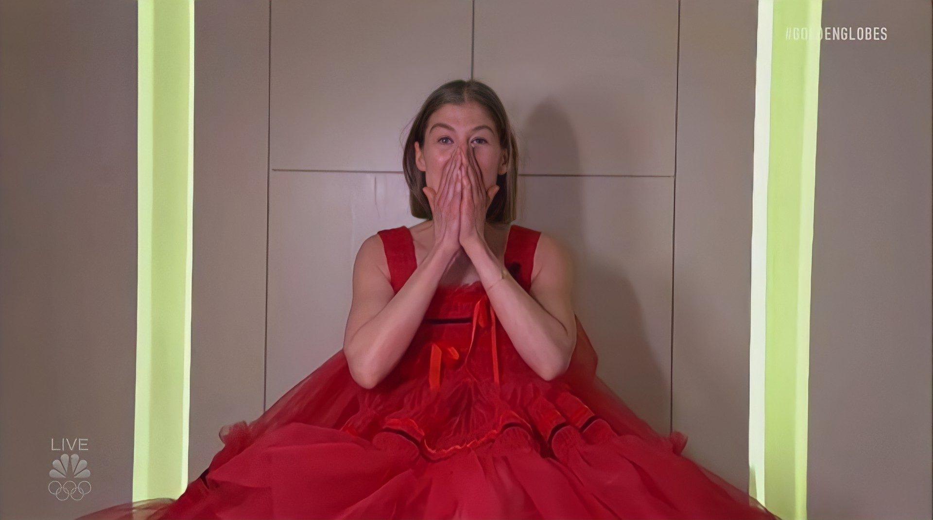 Foto da atriz Rosamund. Uma mulher branca, de cabelo liso, na altura dos ombros e loiro. Ela veste um vestido vermelho cheio de babados. As mãos estão na boca expressão surpresa. O fundo é cinza.