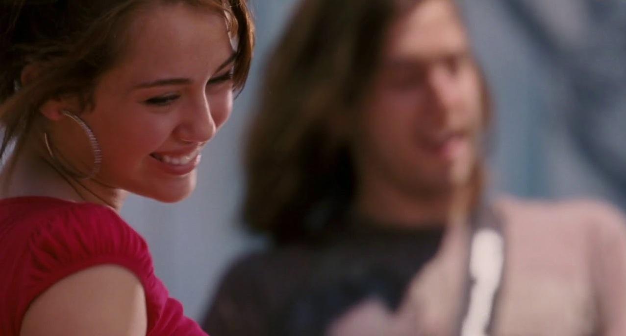 A foto tem um formato retangular com cores vivas e frias. A Esquerda da foto, a personagem feminina Miley Stewart apresenta um semblante feliz e um sorriso no rosto. Seu cabelos castanhos escuros estão presos e uma franja recai sobre o lado esquerdo de seu rosto. Miley veste uma blusa vermelha de manga curta e um brinco médio de argola prata. A direita da imagem, em desfoque, o guitarrista da banda, de cabelos longos castanho claro, usa uma camiseta cinza claro.