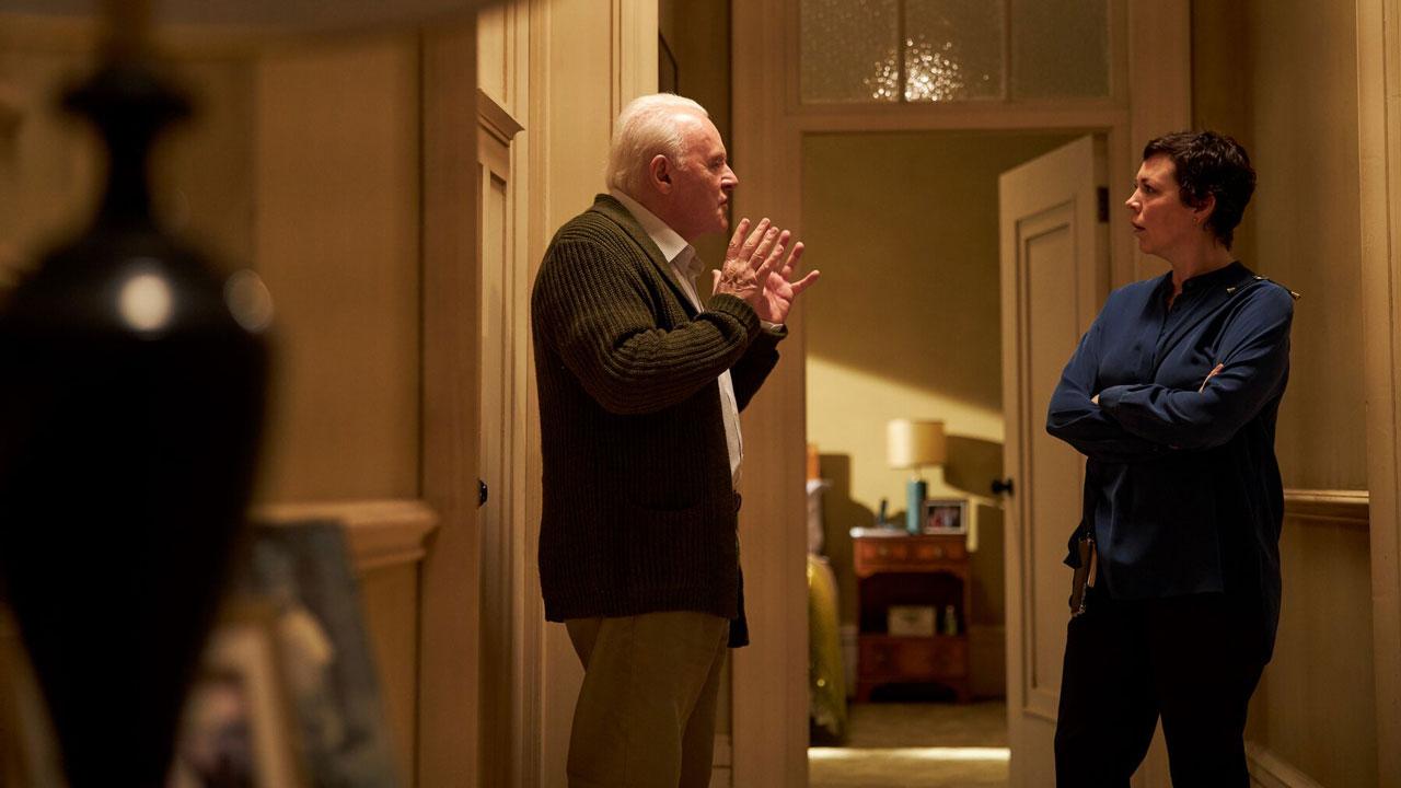 Cena do filme Meu Pai. Nela, vemos Anthony Hopkins e Olivia Colman discutindo num corredor claro, paredes cor de creme, um abajur preto desfocado e uma porta aberta ao fundo. Anthony é um homem branco, idoso, cabelos grisalhos, veste blusa verde e calça bege, e tem as mãos abertas, gesticulando. Olivia é uma mulher adulta, branca, cabelos pretos curtos, veste roupa azul e tem os braços cruzados.