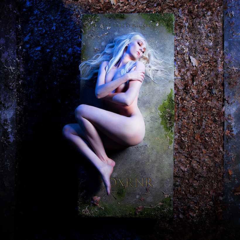 """Capa do álbum """"Death By Rock And Roll"""", do The Pretty Reckless. Taylor Momsen, líder e vocalista da banda, está sendo vista de cima, nua, prostrada em cima de um túmulo de pedra coberto por musgo, com uma luz branca vindo da direita e uma luz azulada da esquerda. Na parte de cima do túmulo é possível ler """"THE PRETTY RECKLESS"""" e na parte de baixo, a abreviação do nome do álbum, """"DXRNR""""."""